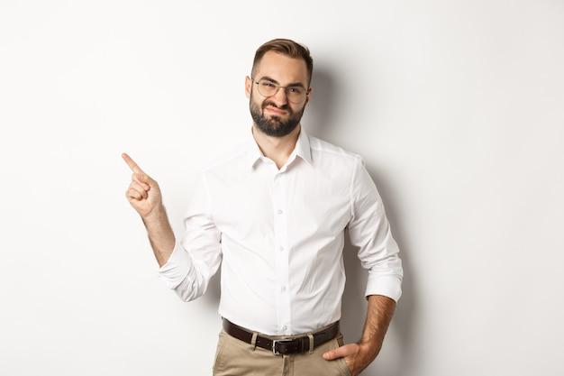 Скептически настроенный предприниматель-мужчина гримасничает, указывая пальцем влево с недовольным лицом, жалуется на