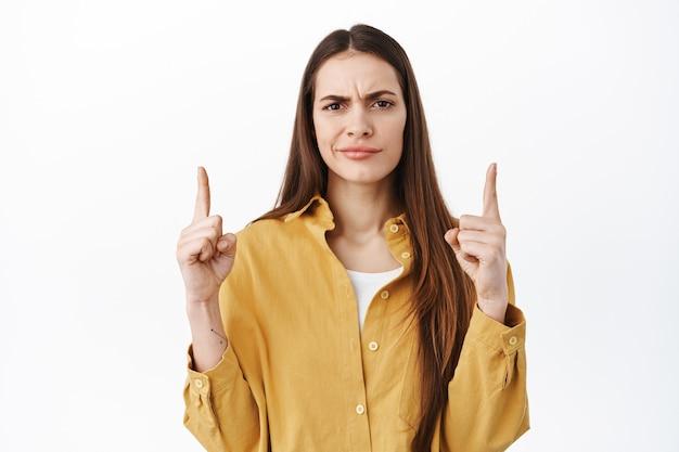 懐疑的または混乱した女性が眉をひそめ、困惑しているように見え、奇妙なものに指を向け、白い壁に疑問を抱き、疑わしく立っている