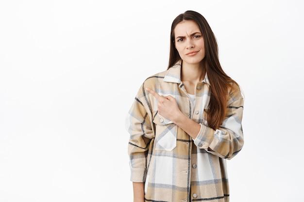 회의적이거나 실망한 젊은 여성이 의심스러운 얼굴로 찡그린 채 이상하거나 의심스러운 것을 옆으로 가리키며 흰 벽에 불만을 품고 서 있습니다.