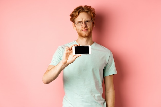 ピンクの背景の上に立って、スマートフォンの画面を水平に表示し、ニヤニヤして眉をひそめている眼鏡をかけた懐疑的な赤毛の男。