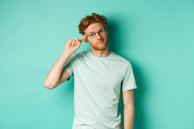 Skeptical redhead man scolding someone stupid or crazy, pointing finger at head and staring at camera, standing over mint background
