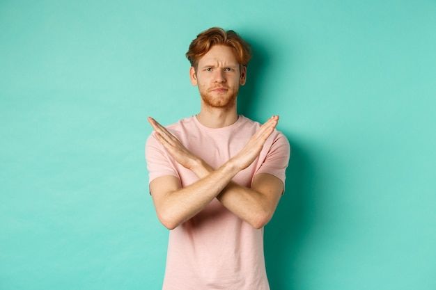 Skeptical redhead man in t-shirt saying no, cross arms on chest and frowning disappointed, prohibit something bad, standing over turquoise background.