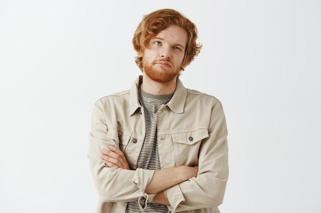 Ragazzo rosso barbuto scettico e riluttante in posa contro il muro bianco