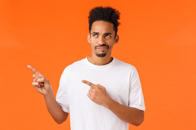 Skeptical and reluctant disappointed african-american man, afro haircut and moustache, pointing looking upper left corner displeased, smirk unsatisfied and judgemental, orange background