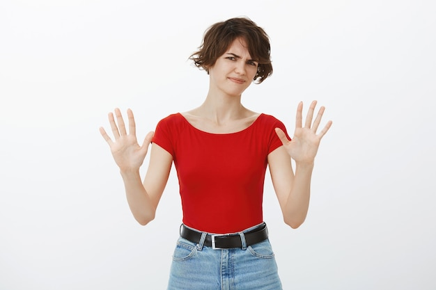Skeptical and reluctant woman raising hands in rejection, refuse offer