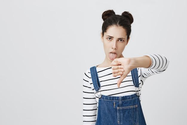 Скептически грубая женщина показывает язык и палец вниз