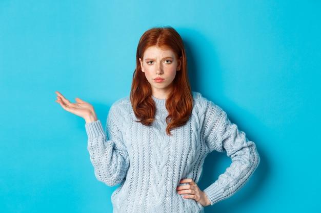 회의적인 10대 소녀는 재미없어 보이는 손을 들어 어떤 제스처를 취하며 부주의한 얼굴로 무언가를 응시하고 파란색 배경 위에 서 있습니다.