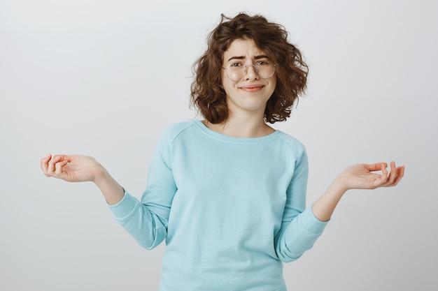 懐疑的な上半身裸の女の子が笑顔で横に手を不注意に上げる