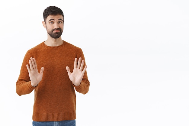 Skeptical and unimpressed handsome male entrepreneur, guy show stop, shaking hands in rejection and smirk, sorry dont want it, refuse participate in strange event, white wall