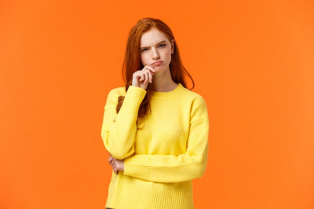 Skeptical and unsure redhead focused, serious-looking female taking hard decision, making choice gift