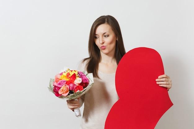 큰 붉은 심장, 흰색 바탕에 아름다운 장미 꽃다발을 들고 회의적인 여자. 광고 공간을 복사합니다. 텍스트에 대 한 장소입니다. 성 발렌타인 데이 또는 국제 여성의 날 개념.