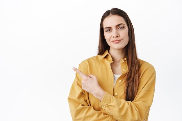 懐疑的な女性は疑わしくて不満を持って笑い、何か足りないものを指さし、コピースペースが残っていることを示し、失望と判断を表明し、白い壁の上に立っています