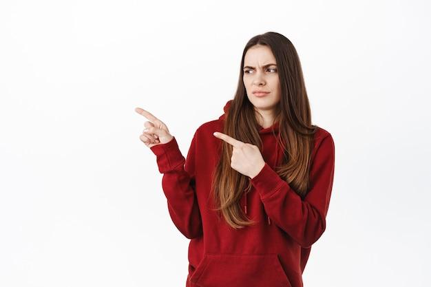 La donna scettica si inclina all'indietro e guarda con disprezzo o dubbio l'affare promozionale del prodotto, indicando e guardando da parte lo spazio della copia con qualcosa di strano, in piedi contro il muro bianco
