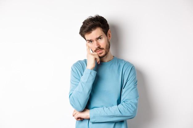 懐疑的な若い男は退屈な顔であなたの話を聞いて、カメラを嫌がって見て、白い背景の上にスウェットシャツで立っています