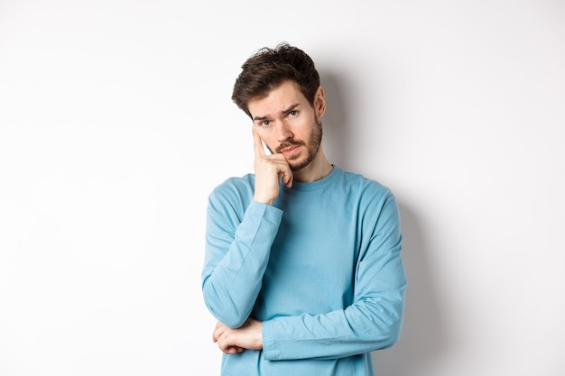 Skeptical young man listening to you with bored face, looking at camera reluctant, standing in sweatshirt over white background