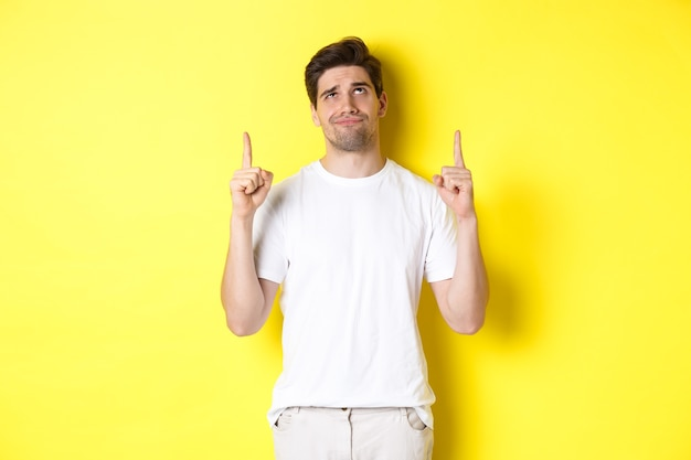 Skeptical young man pointing and looking up at something bad, judging offer, standing over yellow background.