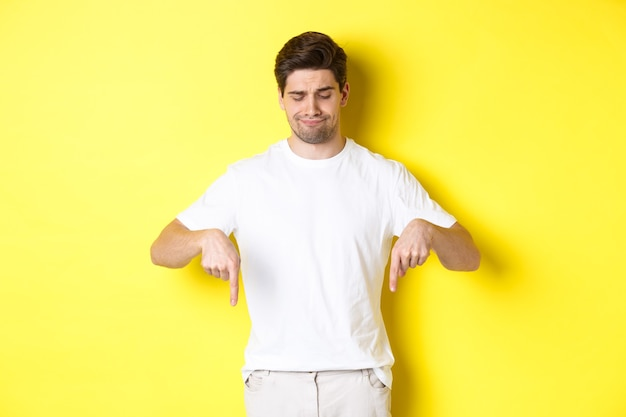 Skeptical young man in white t-shirt, pointing and looking down upset, disapprove and dislike product, standing over yellow background