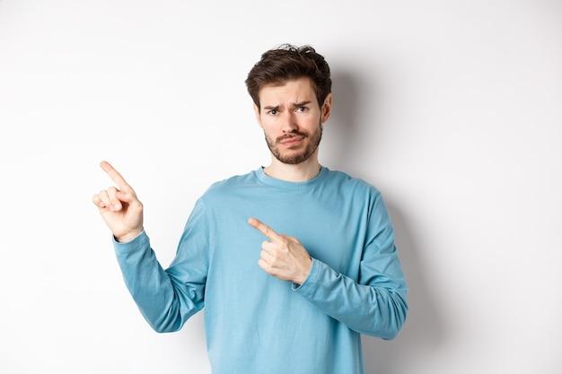 불만족 찡그린 수염을 가진 회의적인 젊은 남자, 인상을 찌푸리고 의심스러운 왼쪽 상단 모서리 로고를 가리키는 흰색 배경 위에 화가 서.
