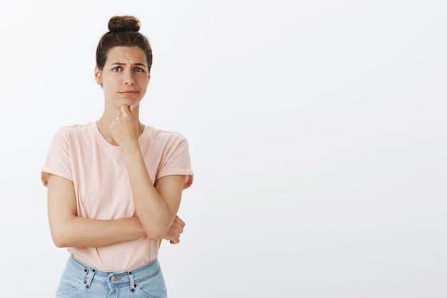 Giovane donna alla moda scettica che posa contro il muro bianco