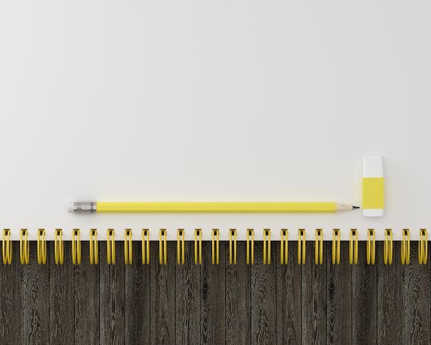 스케치북 및 노란색 파스텔 연필, 나무 배경 지우개 최소한의 작업 공간입니다.