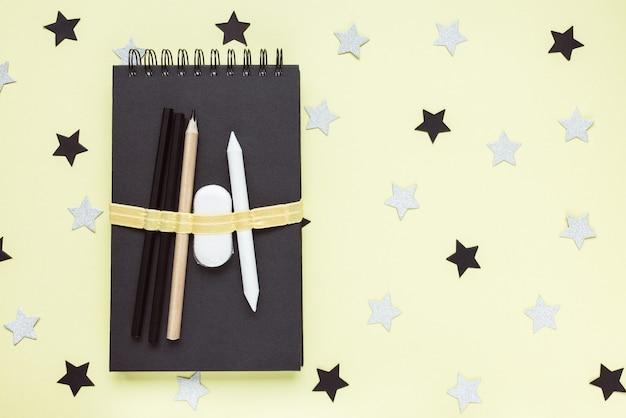 Sketchbook, charcoal pencils, eraser on desk workspace.
