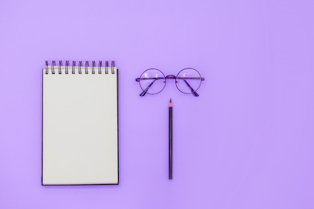 Спираль sketchbook макет на абстрактный фон. очки и черный карандаш.