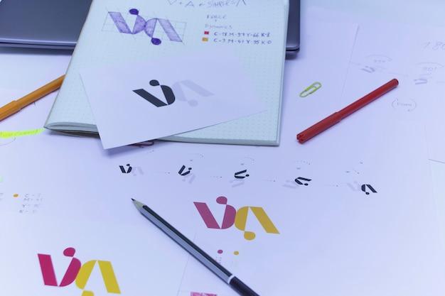 종이에 인쇄된 로고의 스케치 및 그림. 랩톱이 있는 테이블에 있는 스튜디오의 로고 디자인 개발.