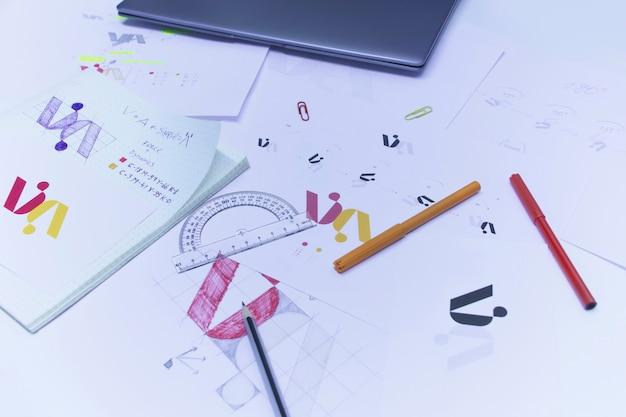 종이에 인쇄 된 로고의 스케치와 그림. 노트북이있는 테이블에 스튜디오에서 로고 디자인 개발.
