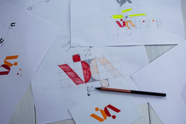종이에 인쇄된 로고의 스케치 및 그림. 테이블에 스튜디오에서 로고 디자인 개발.