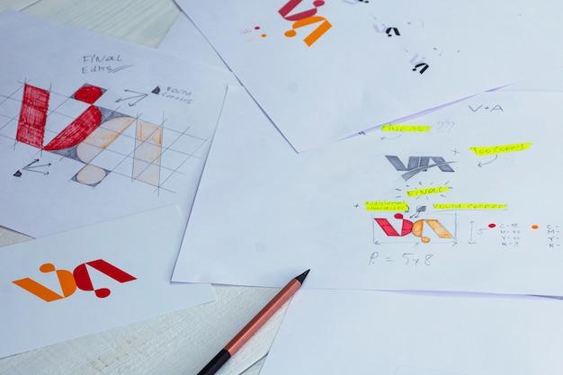 종이에 인쇄 된 로고의 스케치와 그림. 테이블 위의 스튜디오에서 로고 디자인 개발.