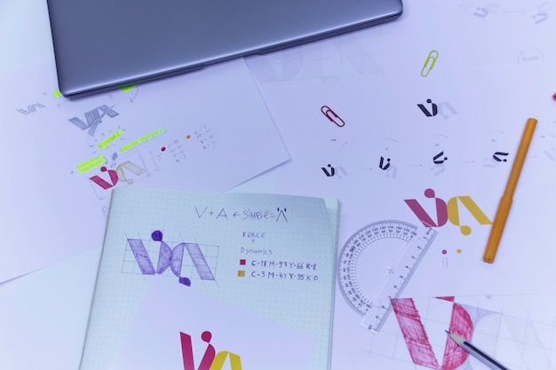 Sketches and drawings of the logo printed on paper. development of logo design in the studio on a table with a laptop.