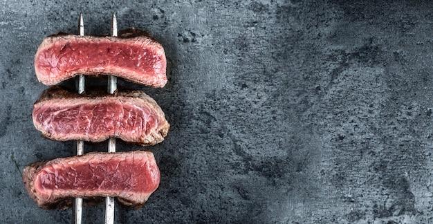 뜨거운 검은 돌 위에 굽은 쇠고기 스테이크를 위에서 본 모습.