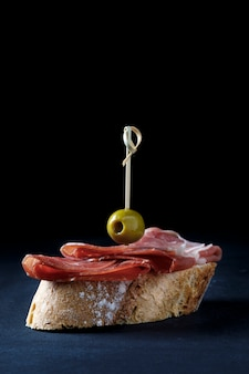 Skewer of iberian ham and olive on dark background