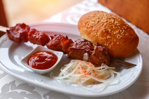 Skewer kebab lying on a plate with sauce