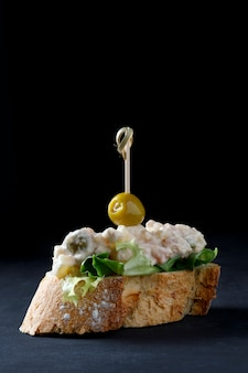Skewer of russian salad and olive on dark background