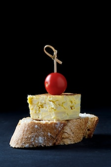 Skewer of spanish omelette and tomato on dark background
