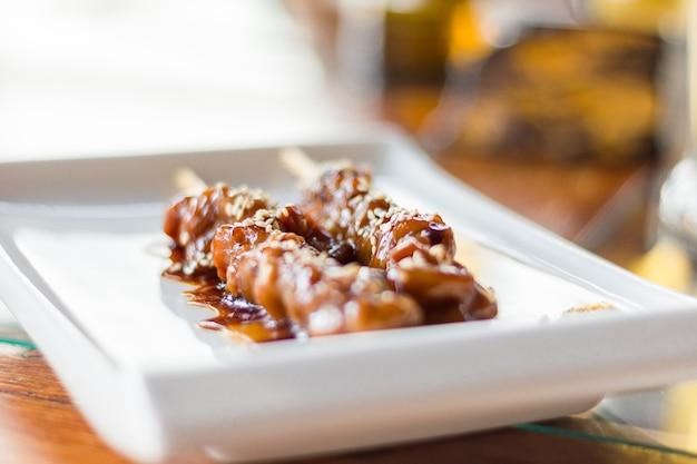 Шашлык из курицы терияки по-японски с кунжутом на прямоугольной тарелке