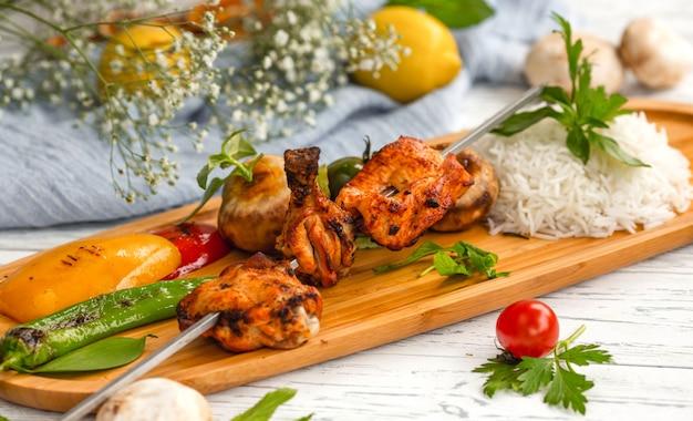 Skewered chicken kebab with rice and vegetables