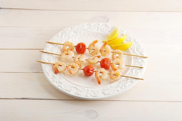 나무 꼬치와 레몬 웨지에 체리 토마토와 꼬치 새우