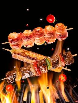 Шашлык из мяса, курицы с беконом и сыром падает на горящий гриль и пламя огня.