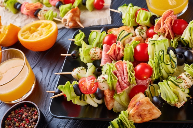 Skewers with chicken meat, zucchini, tomatoes, mozzarella balls, salami slices, olives on a black plate on a wooden table with orange juice in glass cups, summer picnic recipe, close-up