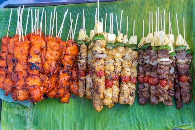 タイのストリートマーケットで販売されているバーベキューのグリル、ピーマン、赤いトマト、肉の串焼きをクローズアップ
