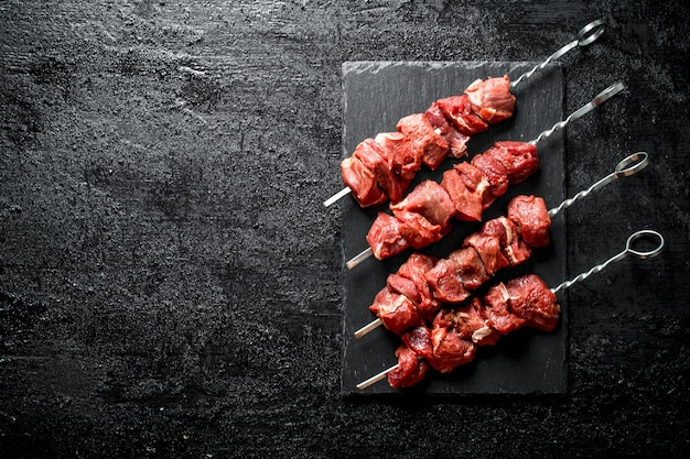Skewers with raw kebab on stone board on black wooden table