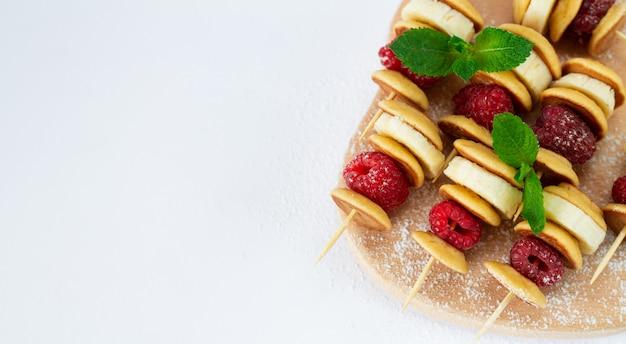 小さなパンケーキ、ラズベリー、バナナ、ミントの葉、砂糖の粉が白い背景で隔離の串。デザートビュッフェラップ