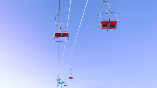 空の背景にスキーチェアリフト。山での冬のアクティブな休息。
