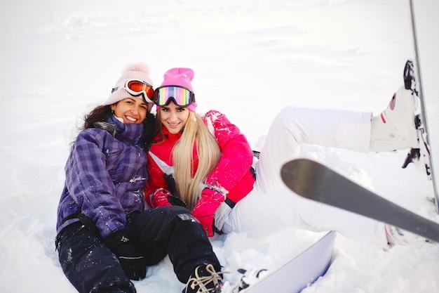 Attrezzatura da sci nelle mani delle ragazze. colori vivaci sui vestiti da sci. le ragazze si divertono insieme.