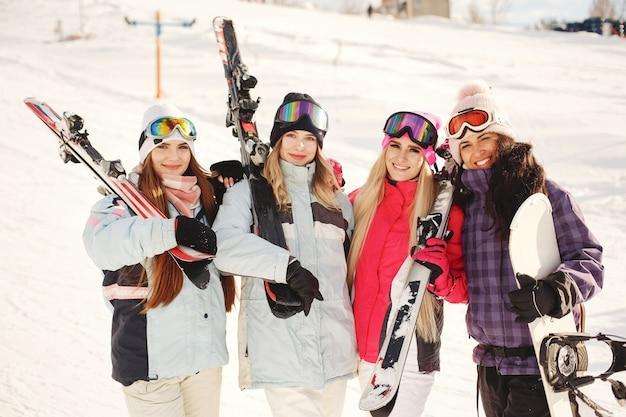 女の子の手にスキー用具。スキーウェアの明るい色。女の子は一緒に楽しい時間を過ごします。