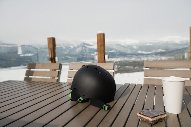 Лыжный шлем со сладкой едой и кофе на столе