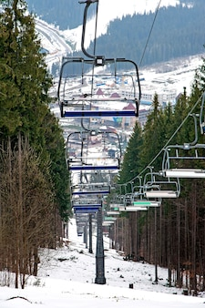 Carpathians의 스키 리조트에서 숲 사이의 스키 리프트 및 스키 피스트