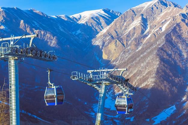 谷の背景に霧があるスキーヤーのためのスキーリフトケーブル、ロープウェイ、およびケーブルウェイ輸送システム。高品質の写真